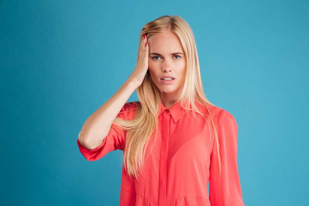 Portrait of a young blonde woman with headache in red dress isolated on a blue background