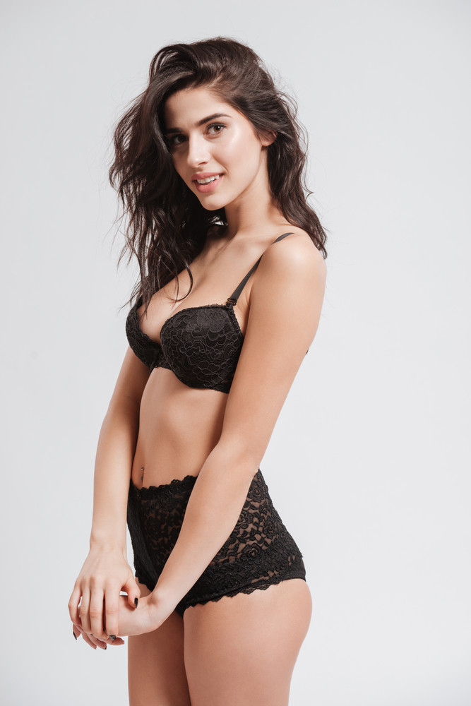 Portrait of a young brunette woman in black lingerie standing and looking at camera isolated on a white background