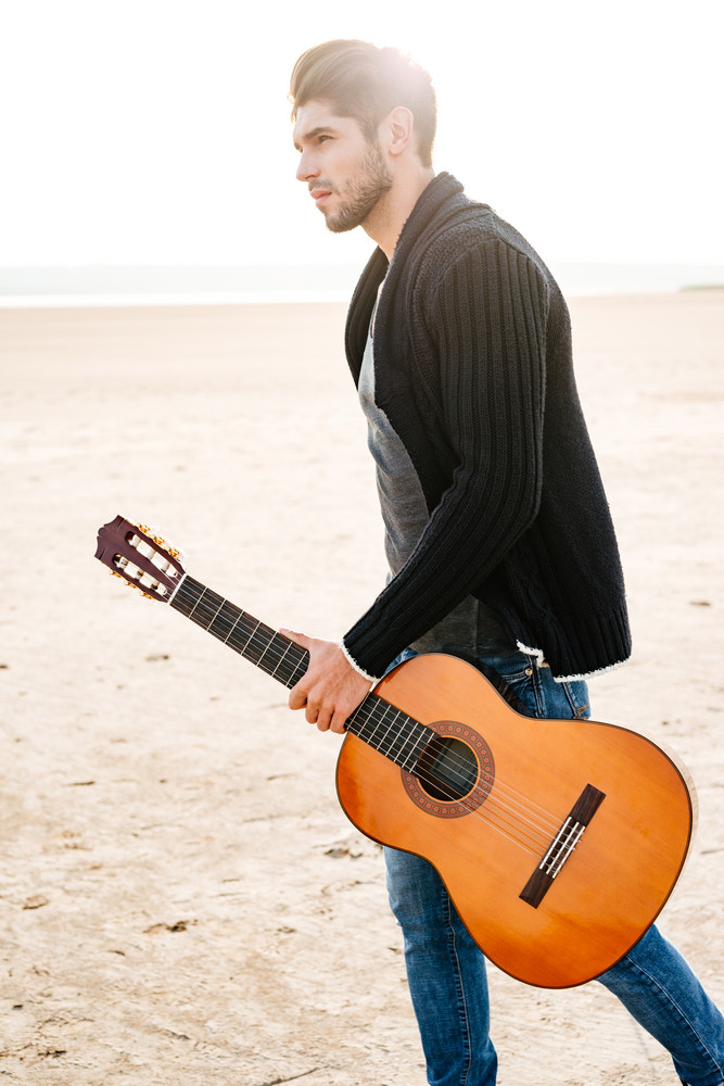 Portrait of a young casual man walking across seashore with guitar