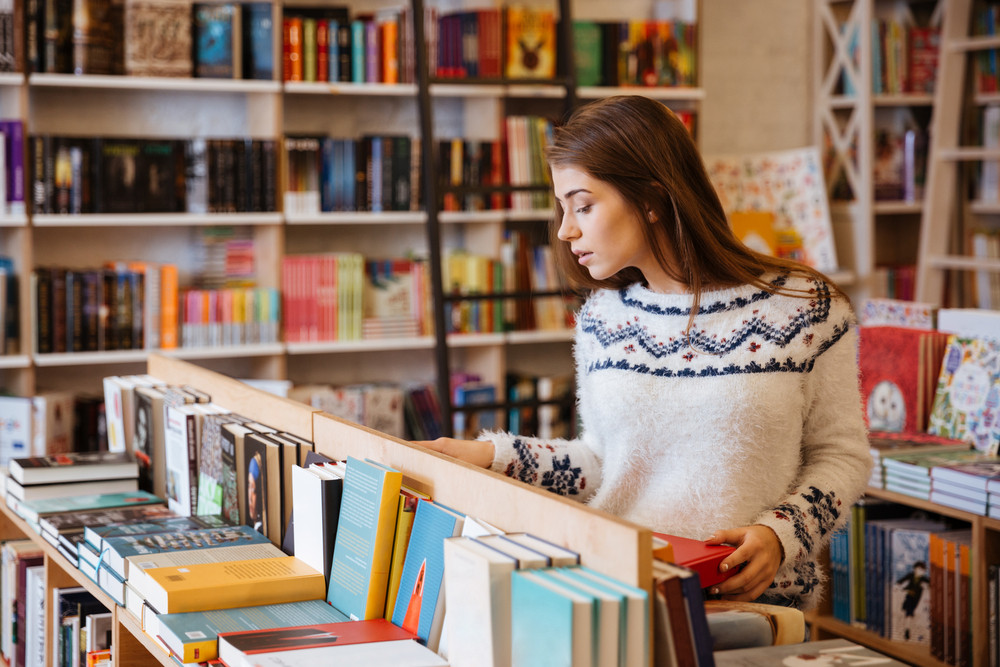 Portrait of a young casual woman searching for a book in bookstore and looking at camera