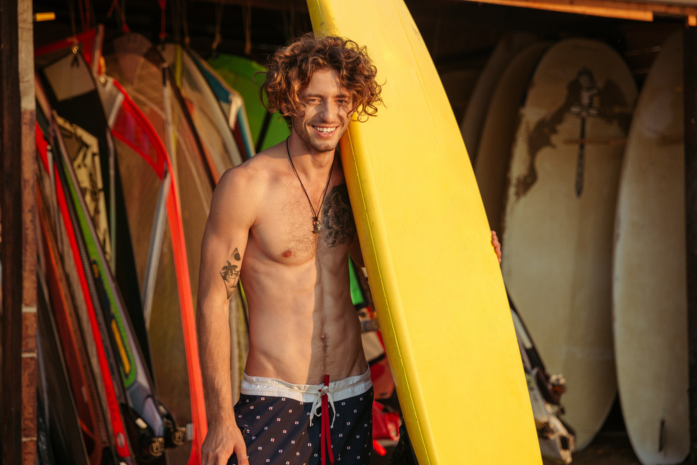 Portrait of a young curly surfer with surfboard