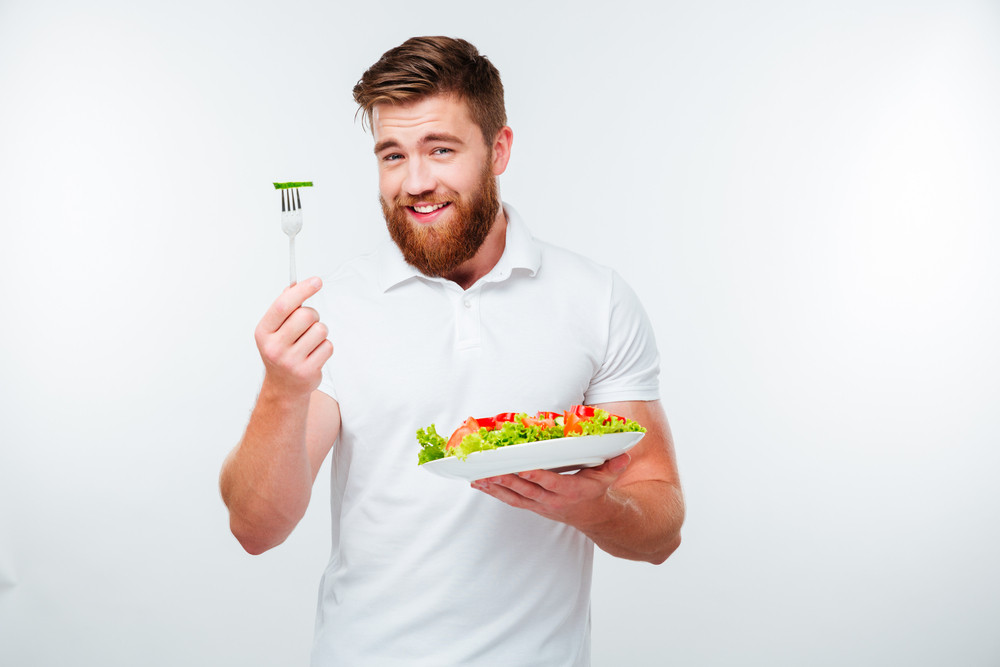 Portrait of a young handsome casual man eating salad isolated on white background