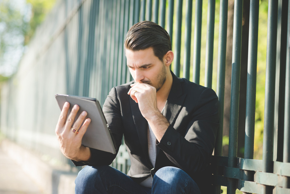 Portrait of a young handsome caucasian man using a tablet connected online, looking down and tapping the screen- technology, social network concept