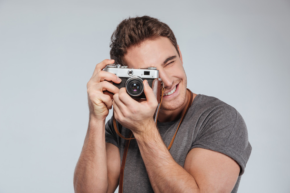 Portrait of a young man photographer with camera taking photo isolated on a white background