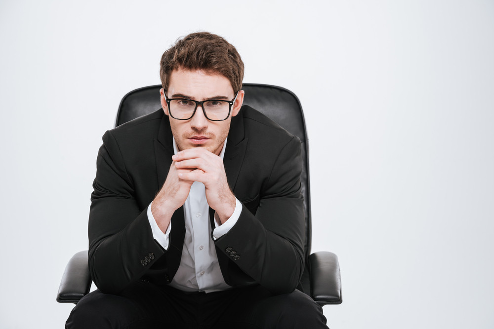 Portrait of a young pensive business man in eyeglasses sitting on a chair with hands on his chin isolated on white background