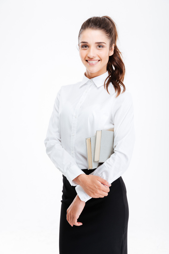 Portrait of a young smiling business woman holding books isolated on white background