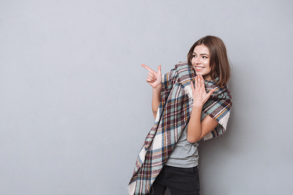 Portrait of a young smiling girl in scarf pointing finger away over white background