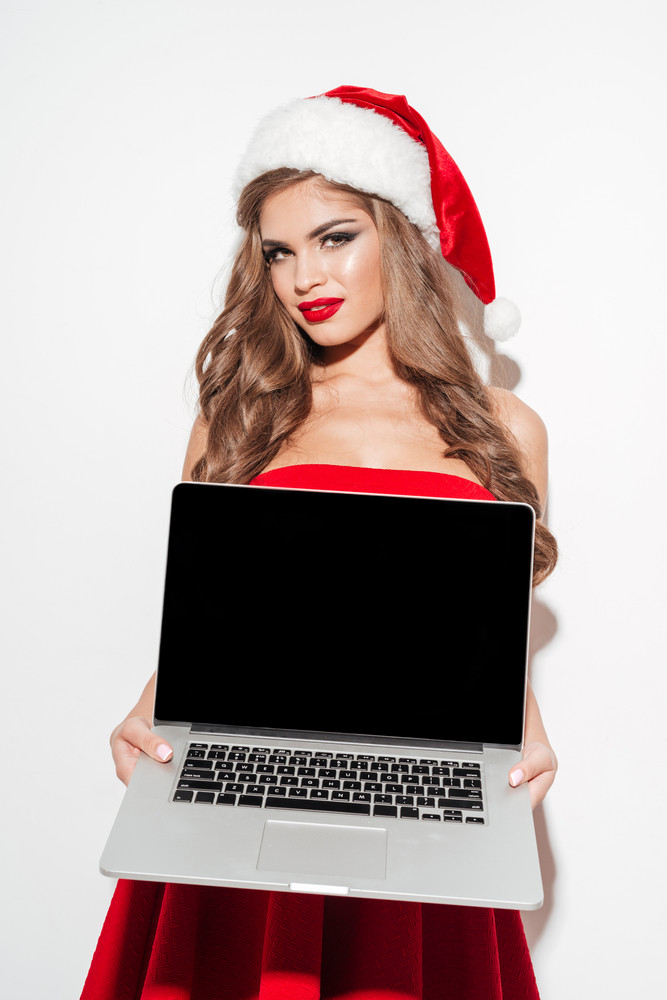 Portrait of a young smiling woman in red santa claus dress and hat holding balnk screen laptop isolated on the white background