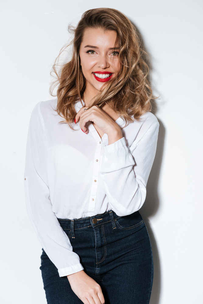 Portrait of a young smiling woman with red lipstick standing over white bakground