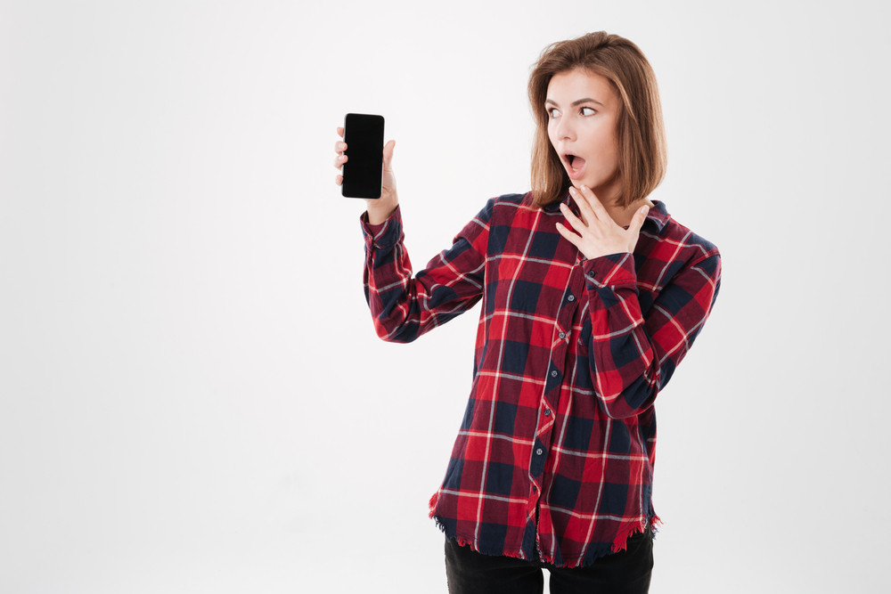 Portrait of a young surprised girl in plaid shirt looking at blank screen mobile phone and covering mouth with palm isolated on a white background
