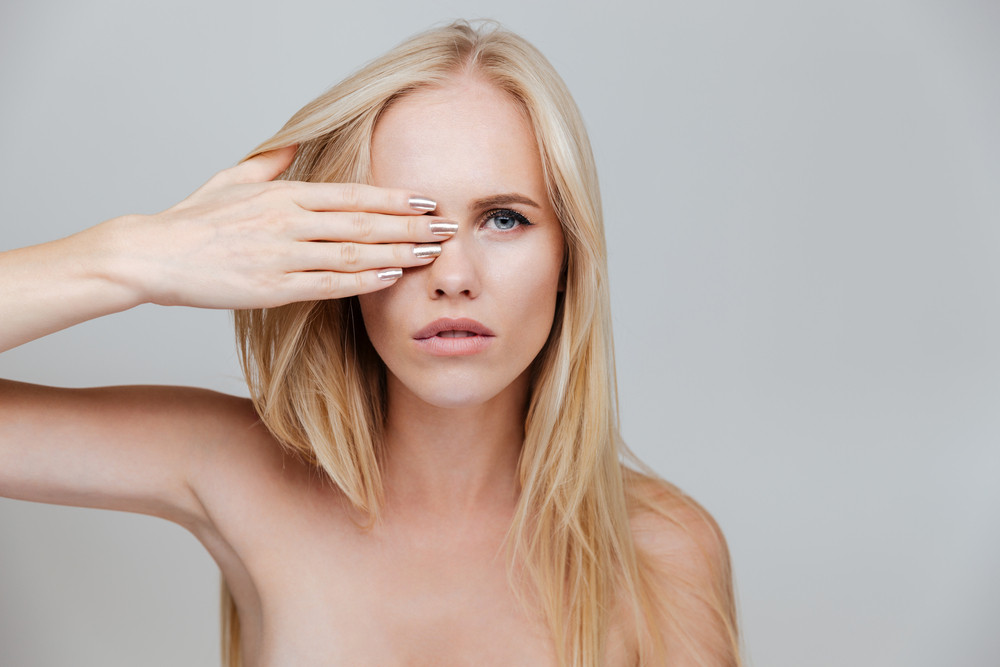 Portrait of a young woman covering her eye with palm isolated on a gray background