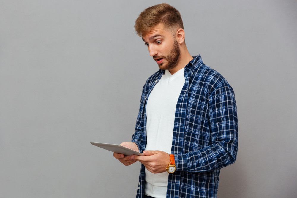 Portrait of amazed casual man using tablet computer over gray background