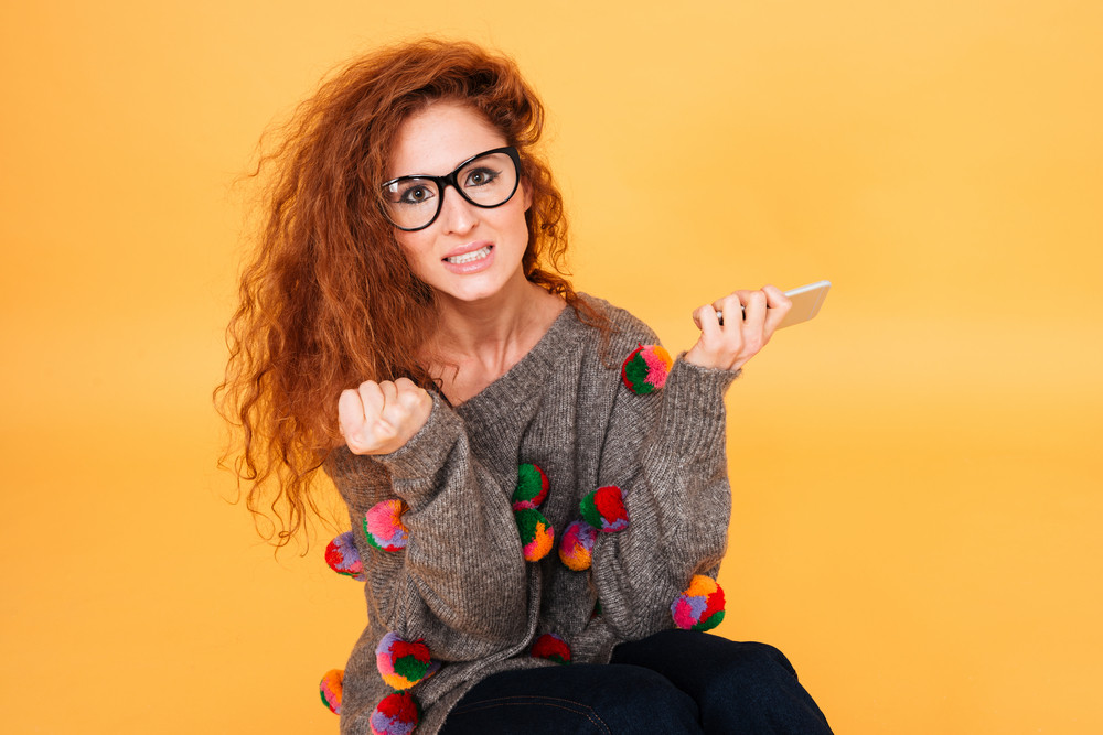 Portrait of an angry casual woman with red hair using smartphone isolated on orange background