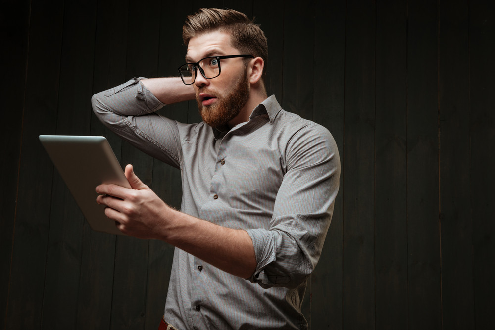 Portrait of an astonished young man in eyeglasses holding tablet computer and gesturing isolated on a black wooden background