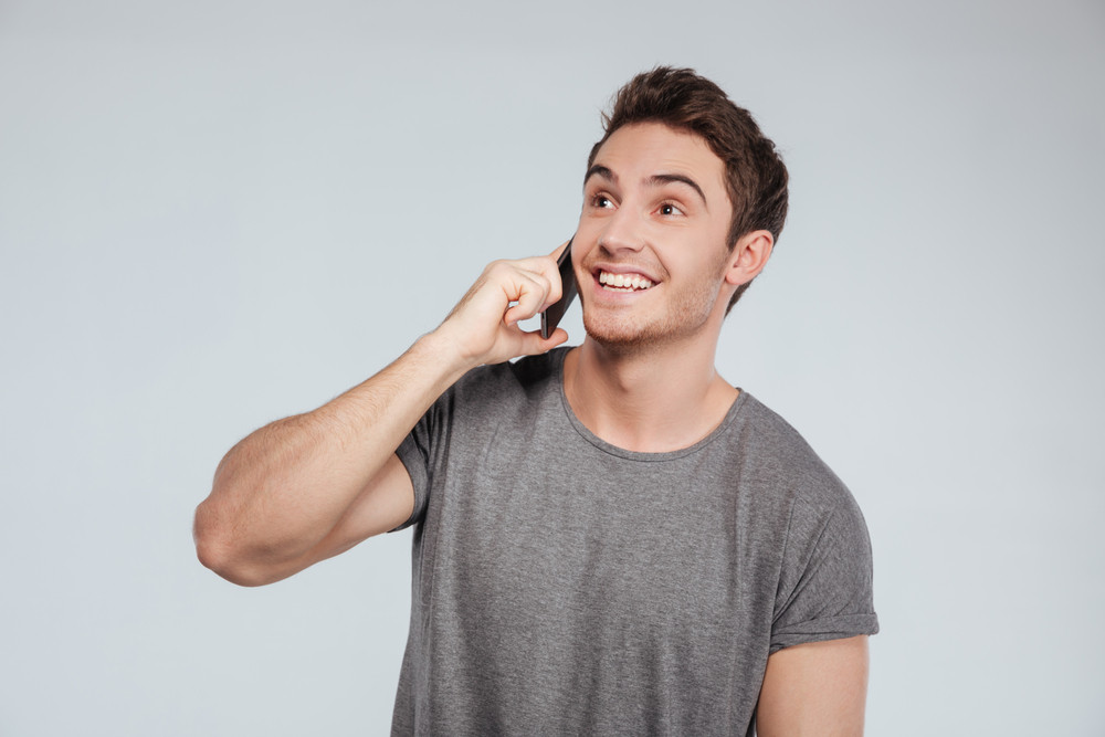 Portrait of an attractive young man talking on mobile phone and smiling over white background
