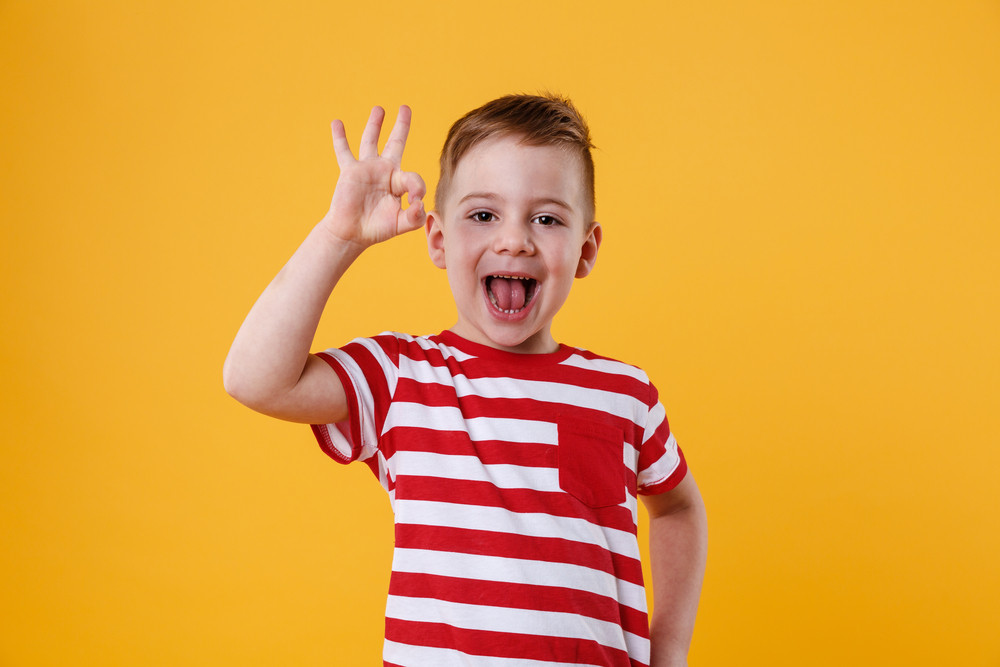 Portrait of an excited little boy standing and showing okay gesture isolated over orange background