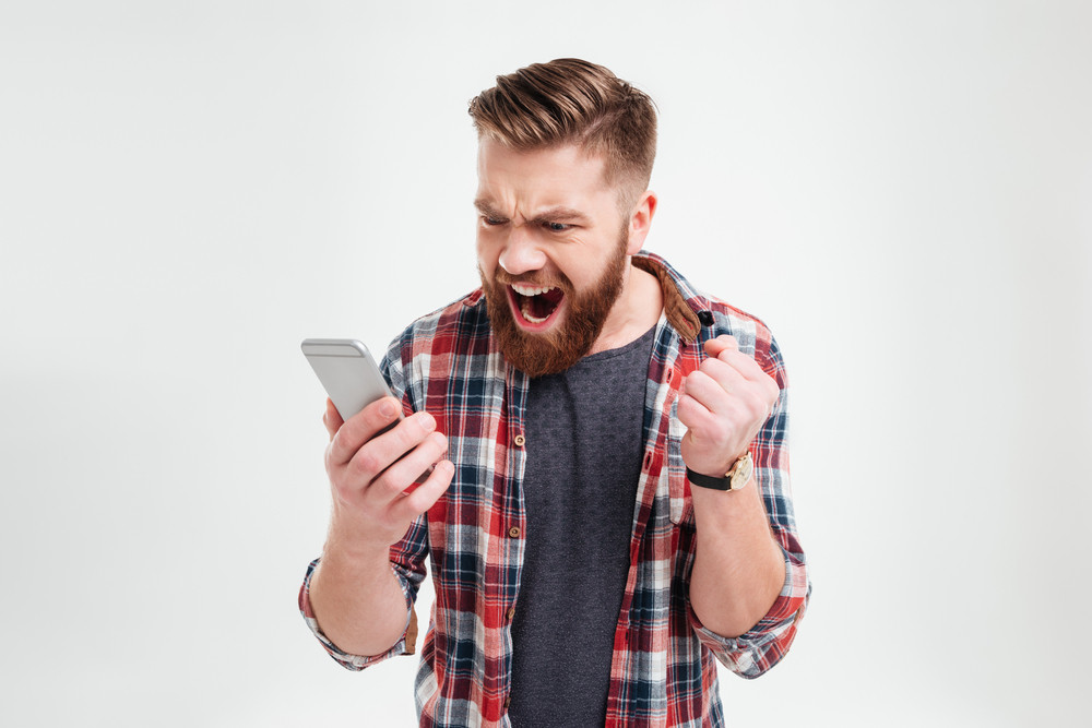 Portrait of angry young man screaming on his mobile phone over white background