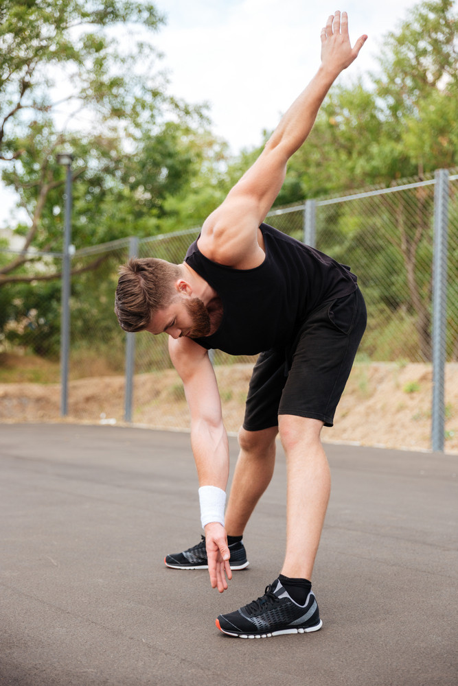 Portrait of athletic bearded man doing stretching exercises outdoors