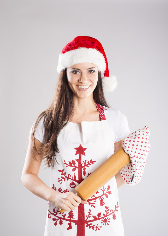 Portrait of attractive woman in chef apron, studio shot with christmas hat