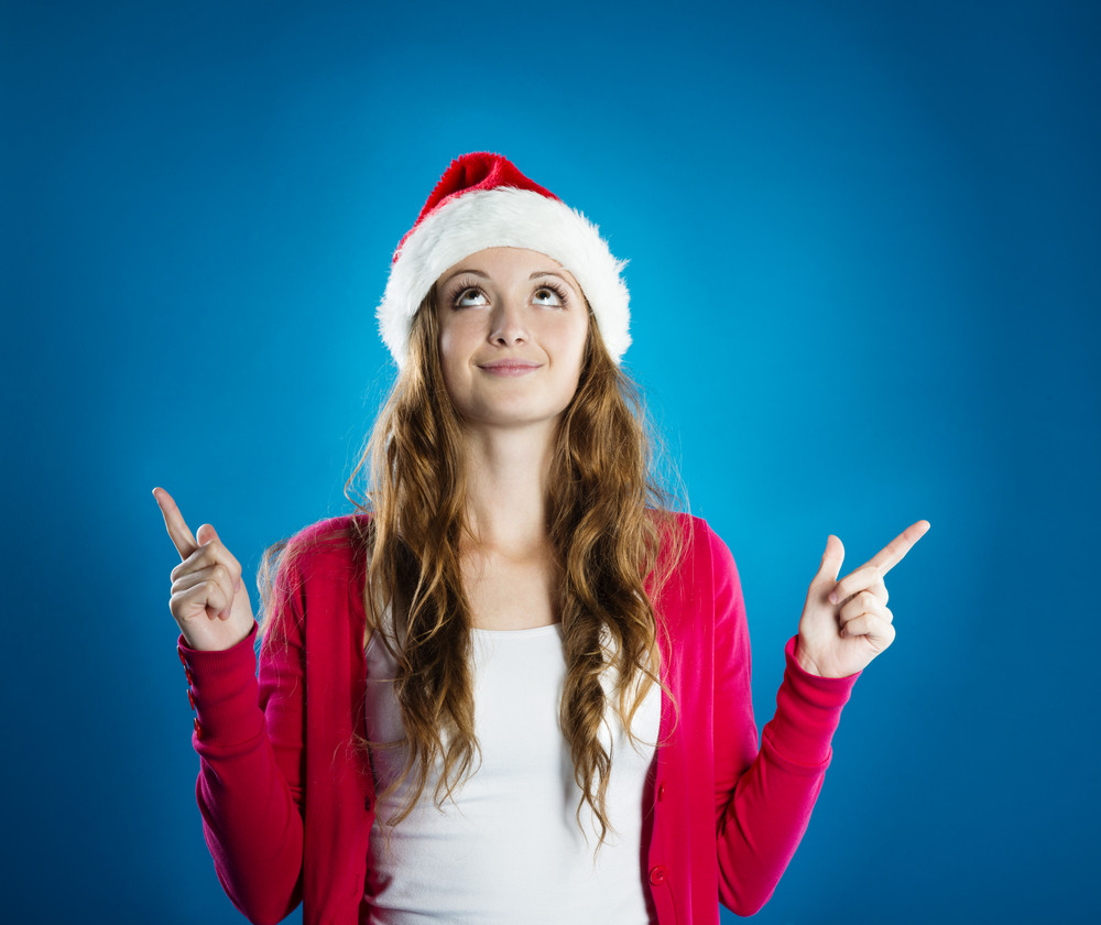 Portrait of attractive woman isolated on blue, studio shot in christmas hat