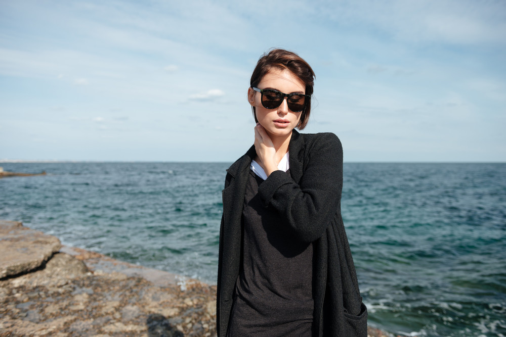 Portrait of attractive young woman in sunglasses and black coat standing near the sea