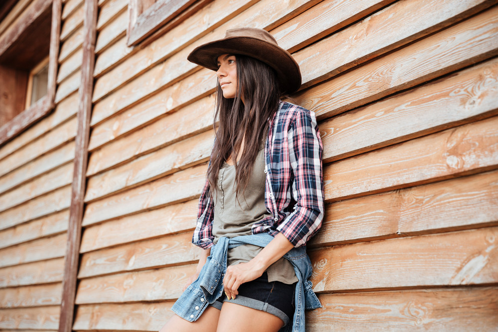 Portrait of attractive young womna cowgirl in hat standing near the house