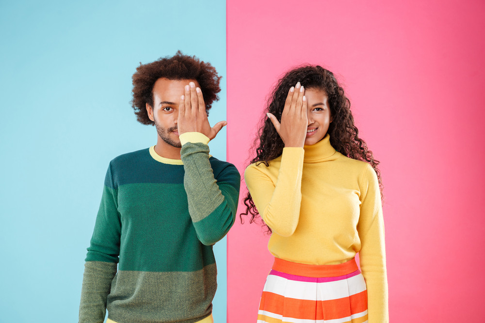 Portrait of beautiful african american young couple covered halves of their faces by hands over colorful background