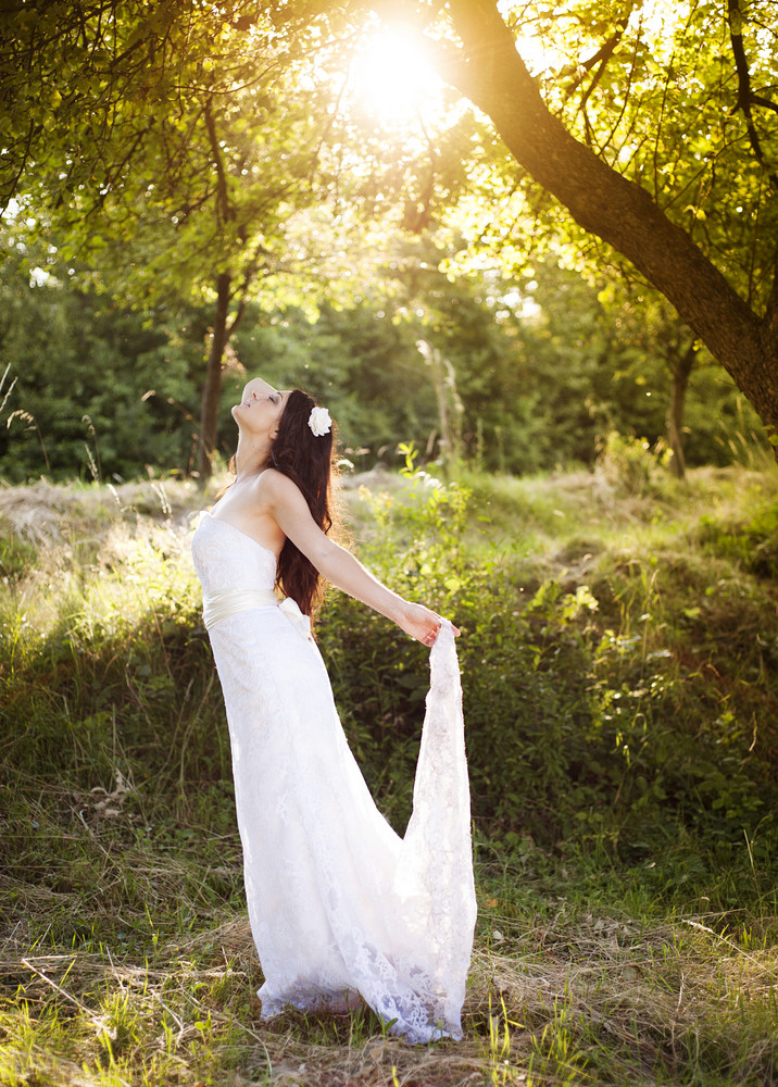 Portrait of beautiful bride in white wedding dress at the meadow
