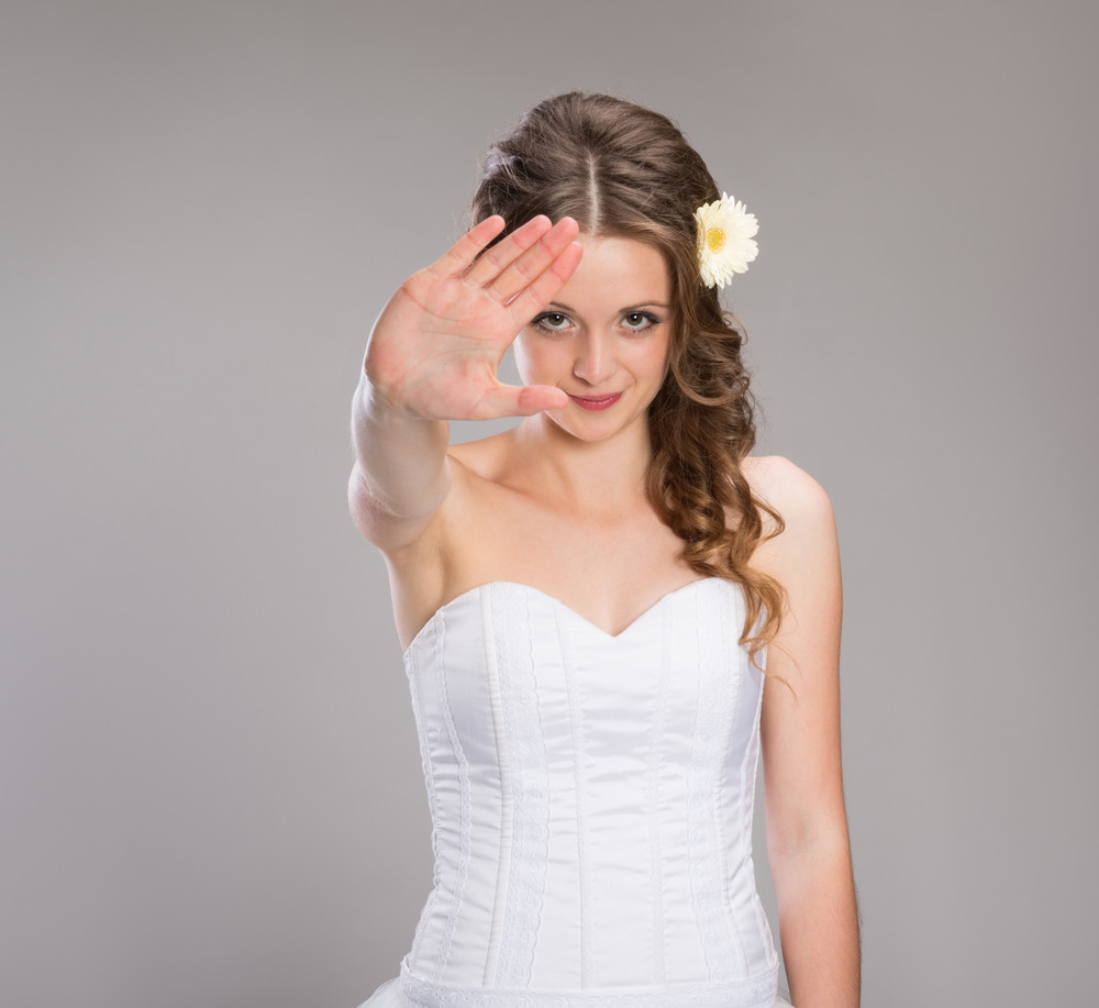 Portrait of beautiful bride posing isolated over gray background