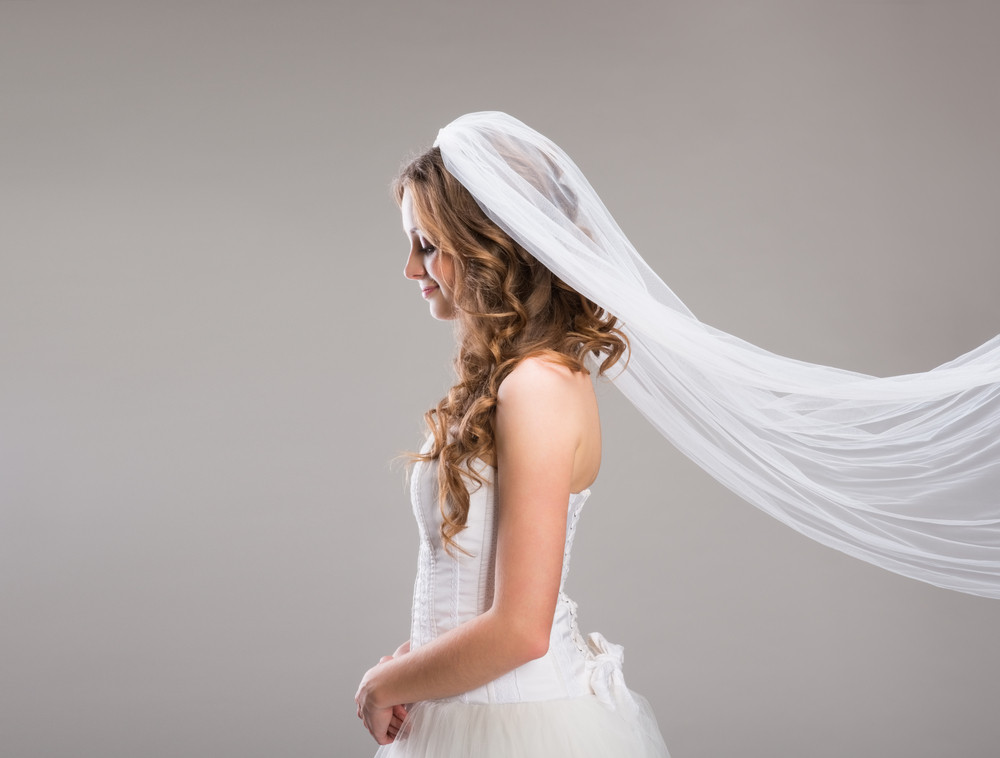 Portrait of beautiful bride with veil isolated over gray background