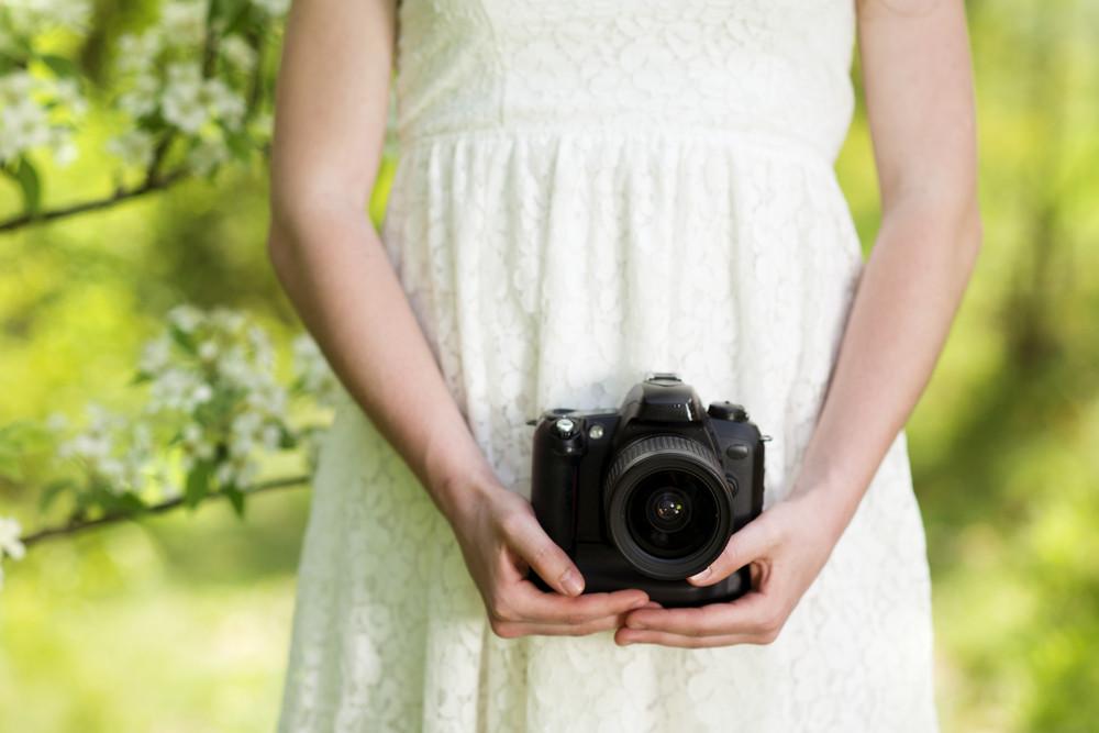 Portrait of beautiful brunette girl making photos at summer green park.