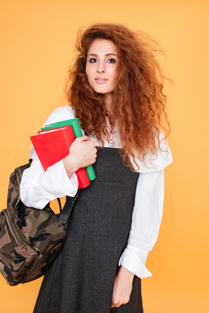 Portrait of beautiful curly young woman holding backpack and books