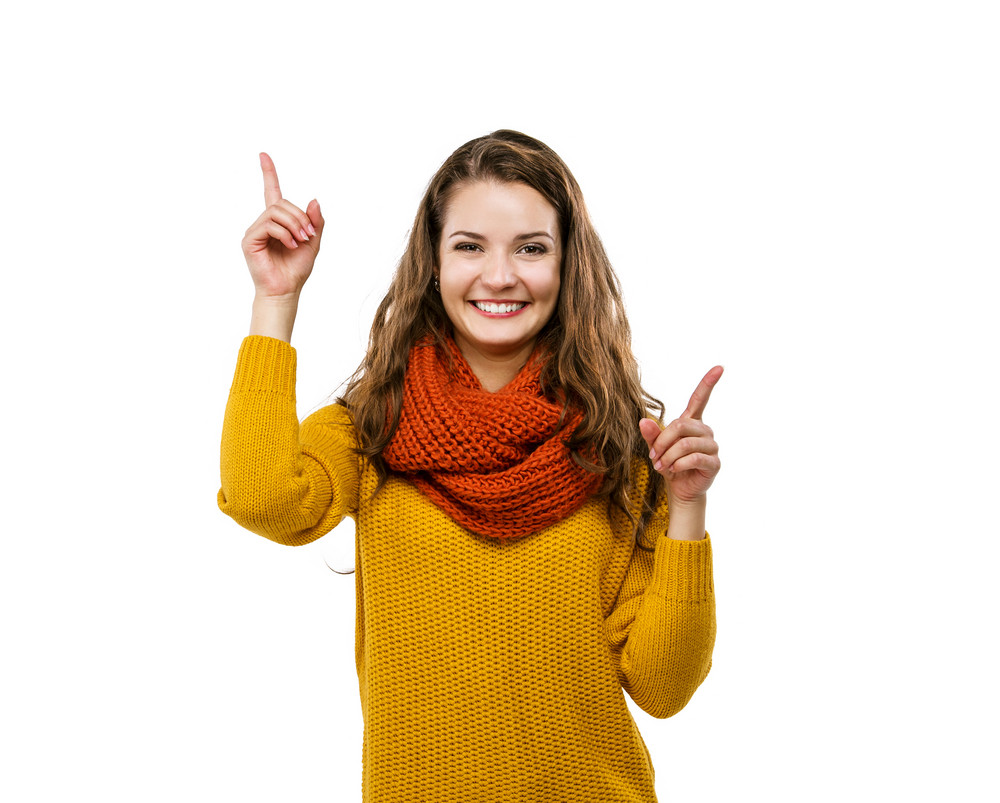 Portrait of beautiful girl in autumn clothes pointing upwards, isolated on white background