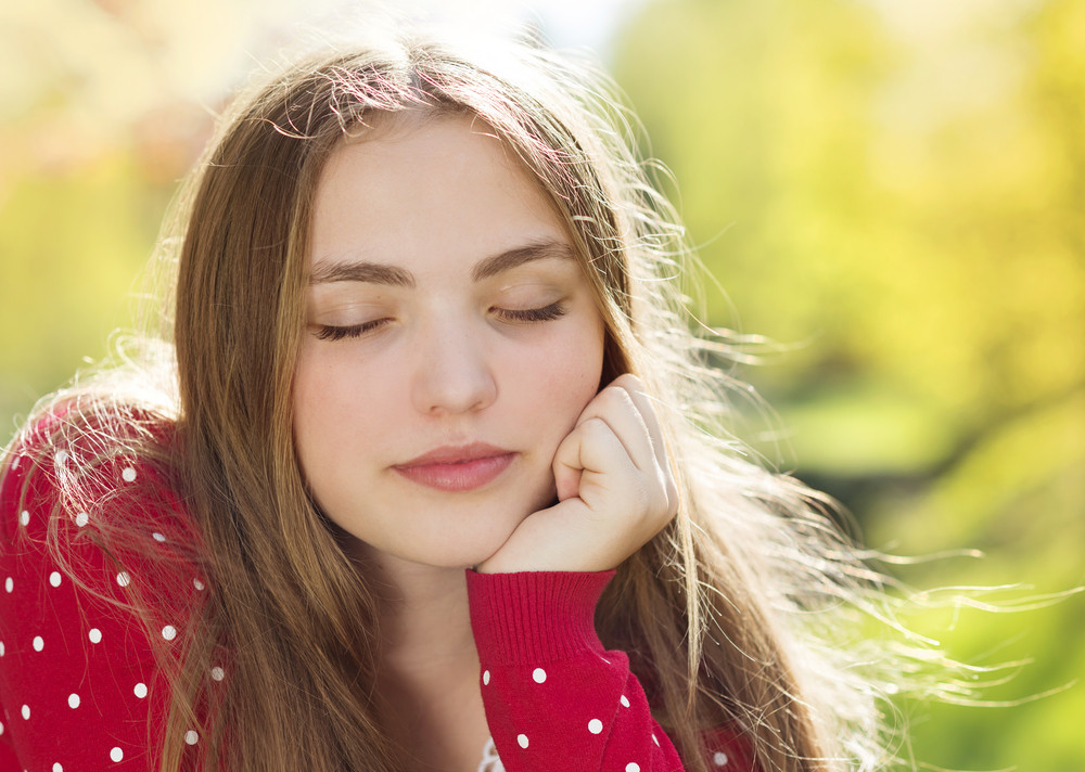 Portrait of beautiful girl in red cardigan daydreaming in green prak
