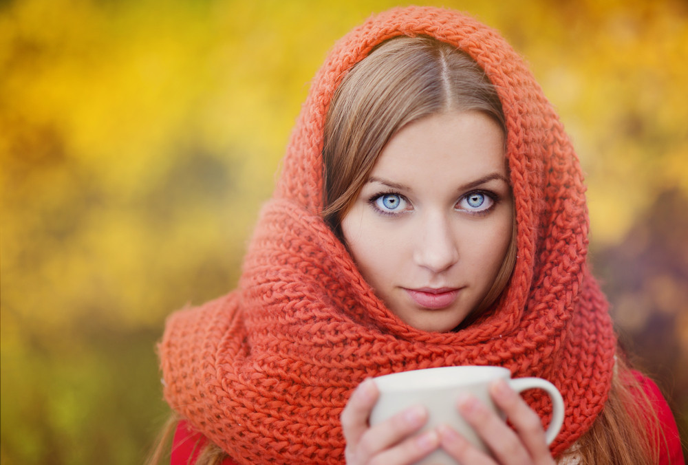Portrait of beautiful girl with scarf and cup with hot drink in autumn nature