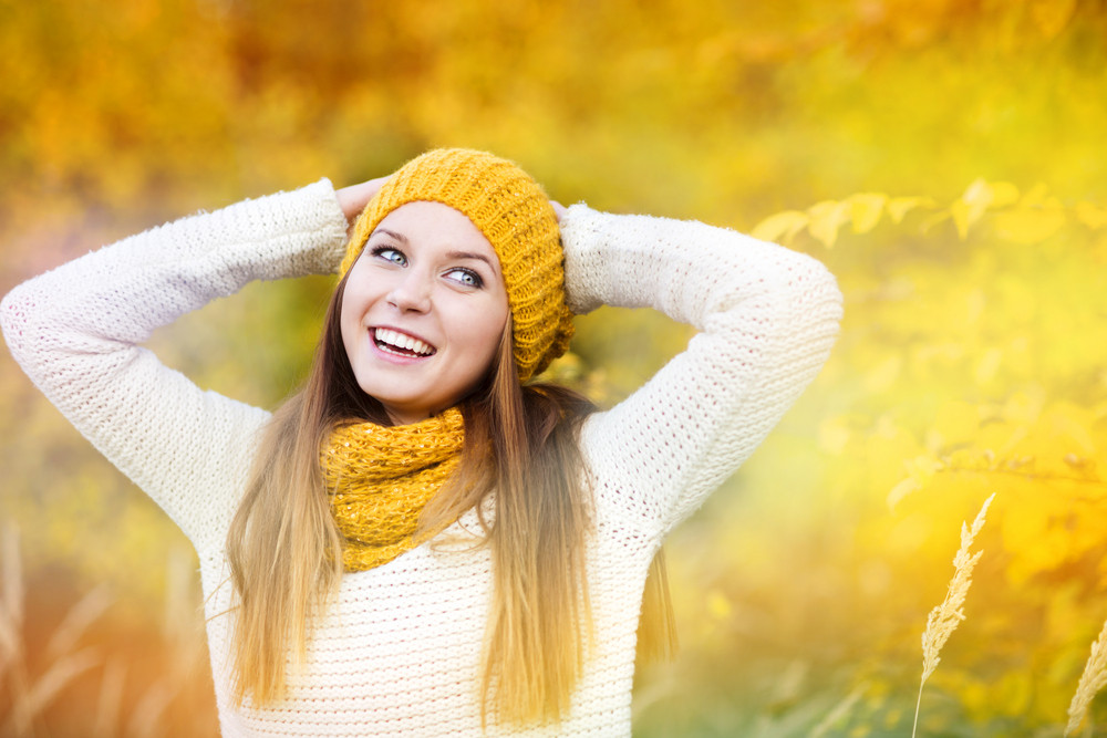 Portrait of beautiful girl with scarf and hat in yellow autumn nature