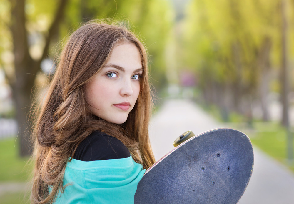 Portrait of beautiful teenage girl with skateboard in green park