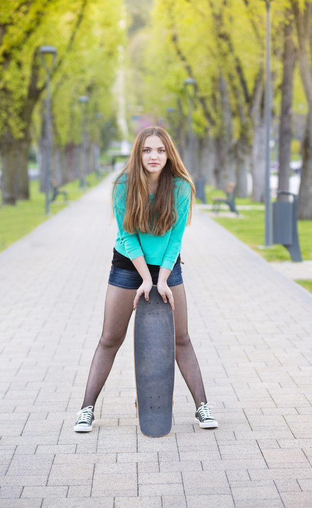 Portrait of beautiful teenage girl with skateboard in green park
