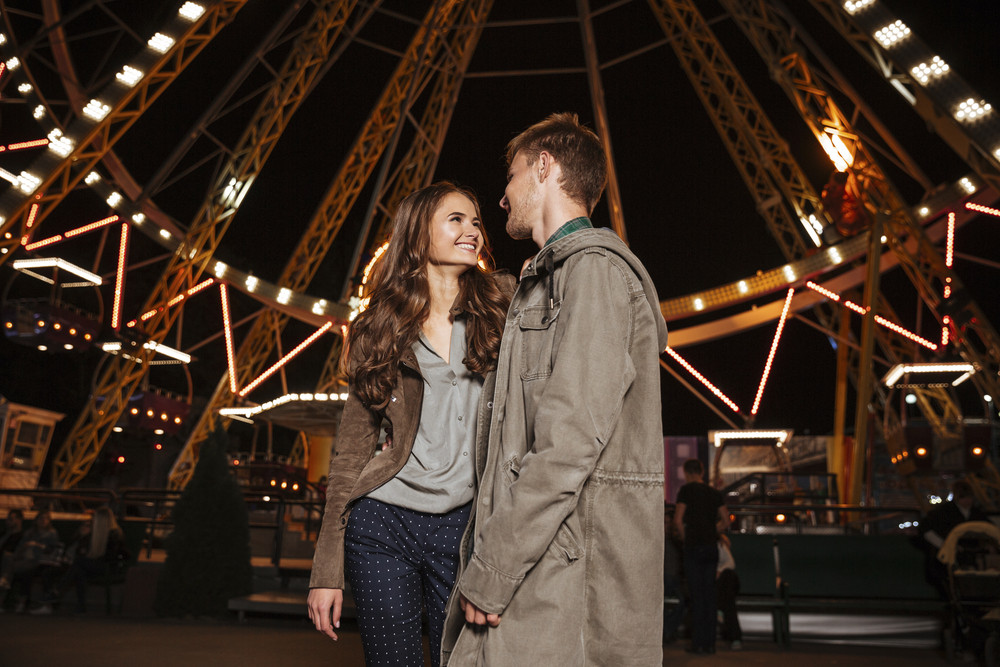 Portrait of beauty couple in amusement park. looking at each other