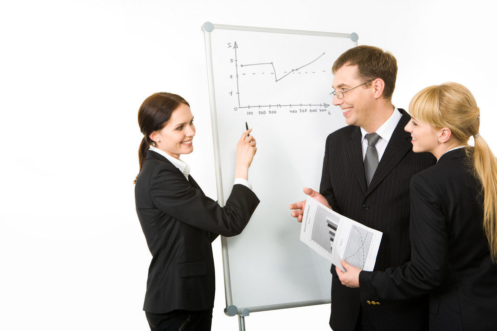 Portrait of business woman explaining her ideas to partners on the whiteboard at seminar