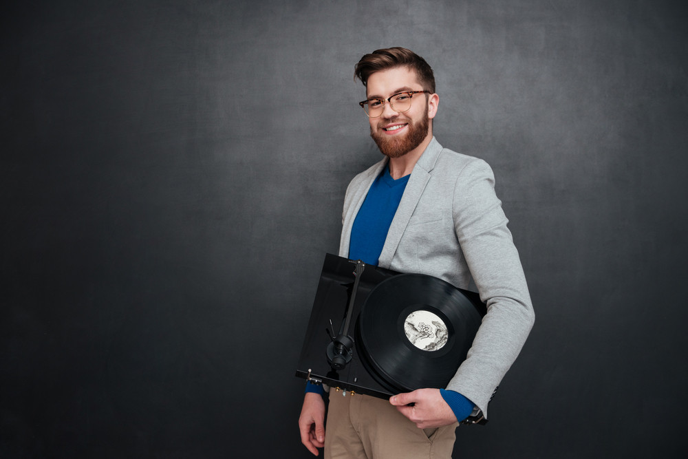 Portrait of cheerful bearded young man in glasses with turntable