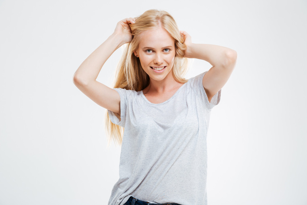 Portrait of cheerful beautiful young woman with blonde hair over white background