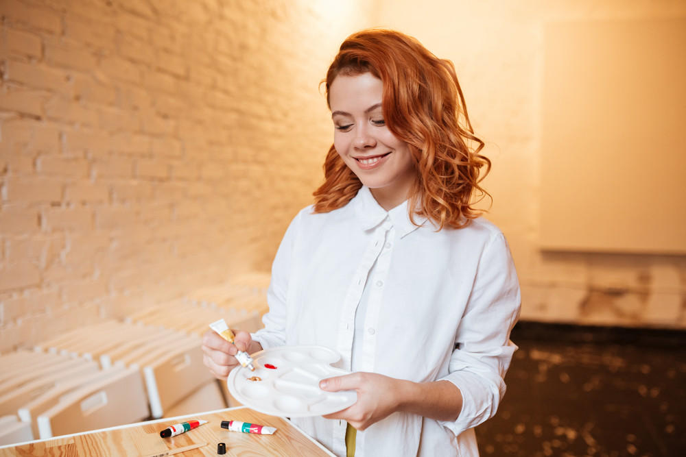 Portrait of cheerful redhead young woman painter with oil paints and palette. Look at palette.