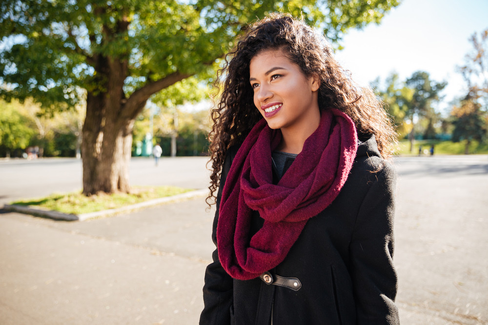Portrait of cheerful young dark skinned curly woman wearing scarf against nature background. Look aside.