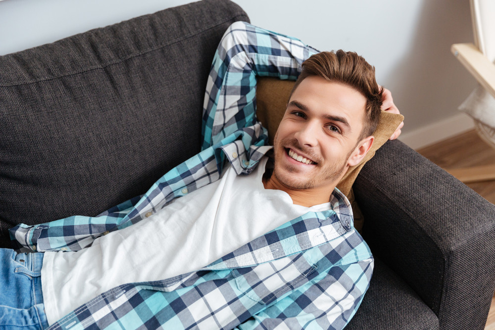 Portrait of cheerful young man dressed in shirt in a cage print lies on sofa at home and looking at the camera.