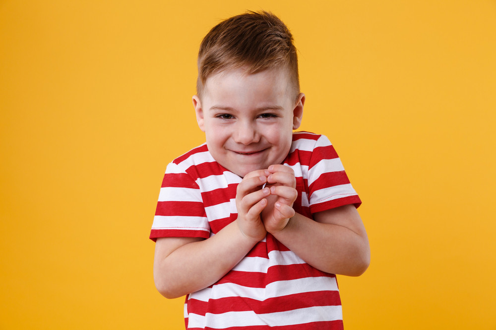 Portrait of clever little boy who's up to something isolated on orange background