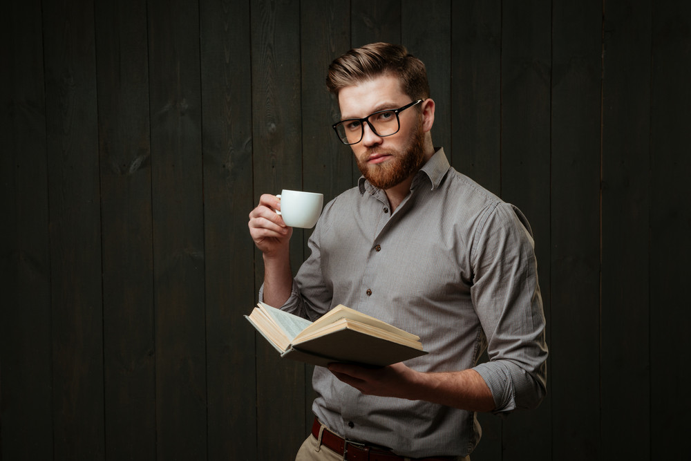 Portrait of concentrated bearded man holding open book and drinking coffee isolated on a black wooden background
