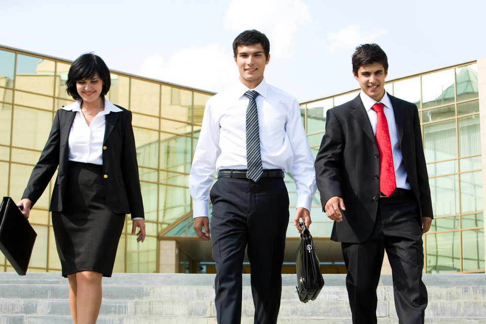 Portrait of confident business group walking outdoors and looking at camera