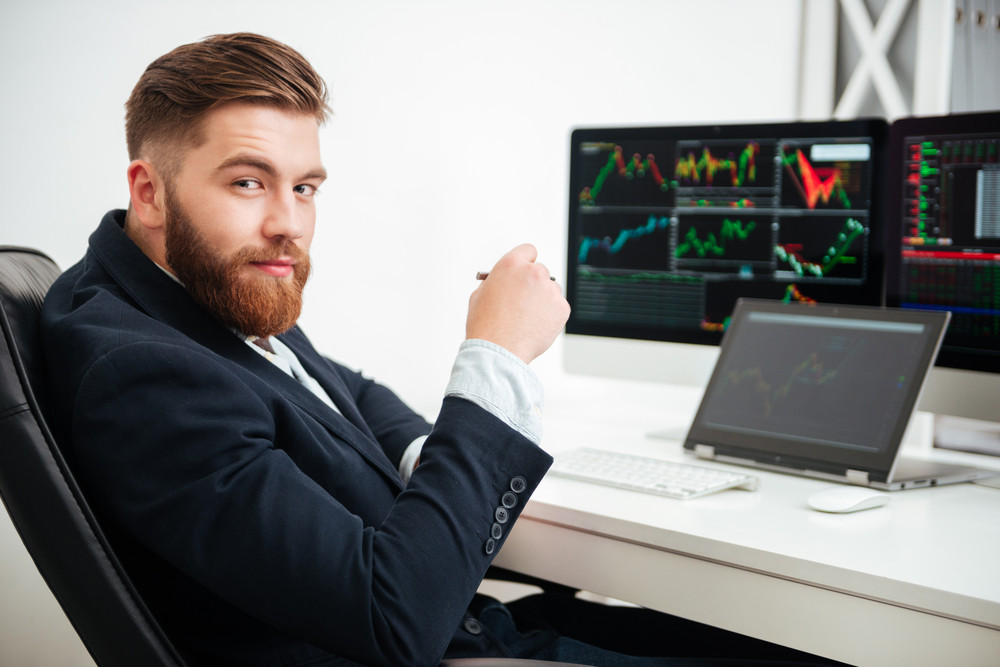 Portrait of confident young businessman sitting and working in office
