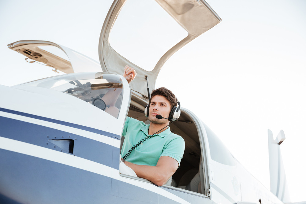 Portrait of confident young man pilot in small plane